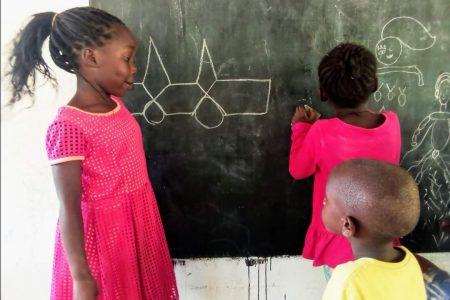 Niños escribiendo en la pizarra